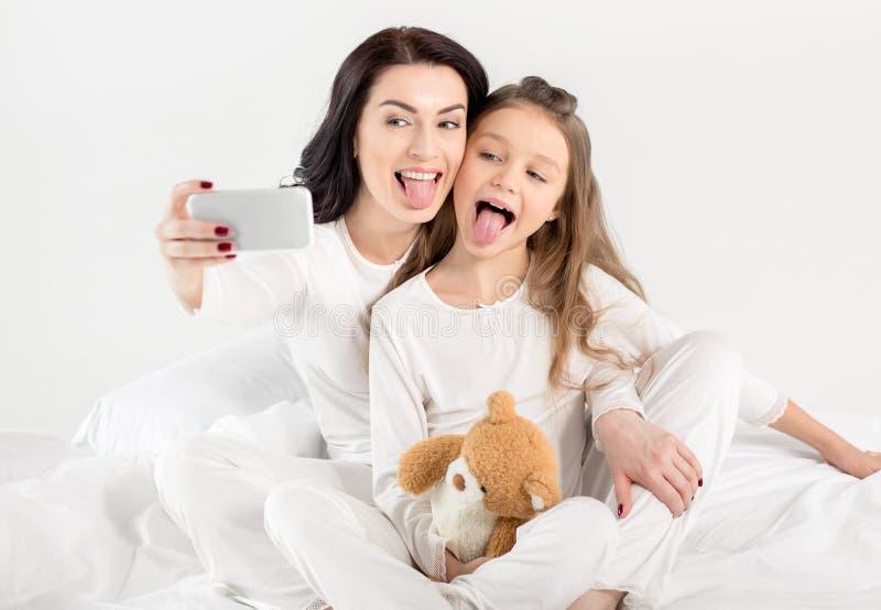 Glückliche Mutter und Tochter in den Pyjamas, die selfie mit Smartphone nehmen stockbilder