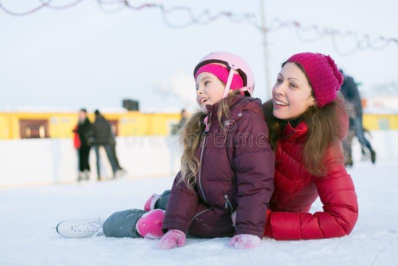 Glückliche Mutter und Tochter, die auf der Eisbahn im Freien sitzt stockbilder