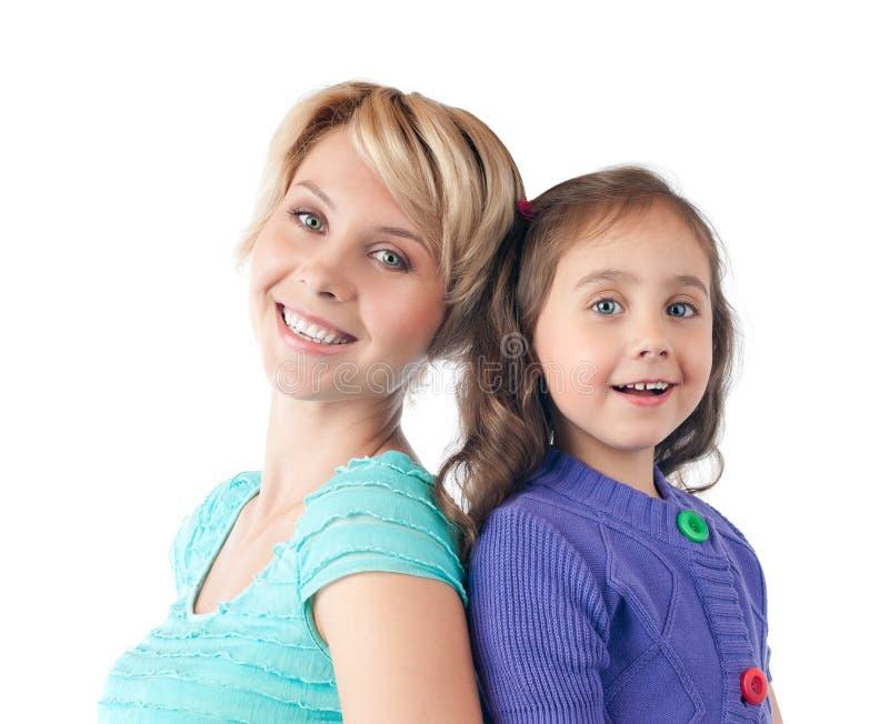 Glückliche Mutter und Tochter, die im Studio lächelt lizenzfreie stockfotografie