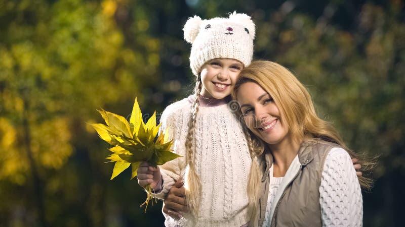 Glückliche Mutter und Tochter, die Kamera, Annahmemitte, Fall lächelt und betrachtet lizenzfreie stockfotografie