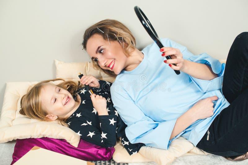 Glückliche Mutter und Tochter haben Spaß zu Hause Mama und Tochter schminken im Schlafzimmer Kids gesunde Kosmetik für Make-up lizenzfreie stockfotografie