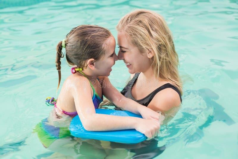 Glückliche Mutter und Tochter im Swimmingpool lizenzfreie stockfotografie