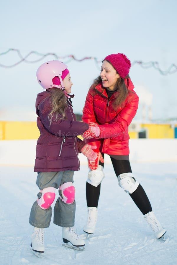 Glückliche Mutter und Tochter laufen an der Eisbahn im Freien eis stockfotos