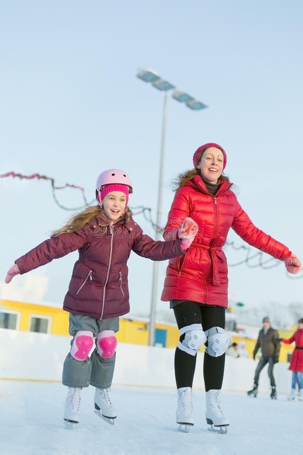 Glückliche Mutter und Tochter laufen Eisbahn an der im Freien eis lizenzfreie stockfotos