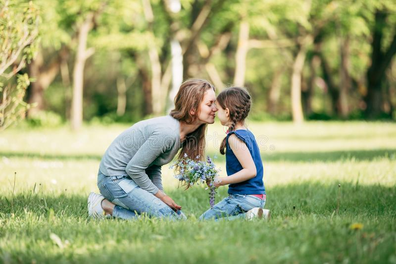 Glückliche Mutter und Tochter mit einem Blumenstrauß von Wildflowers lizenzfreies stockbild