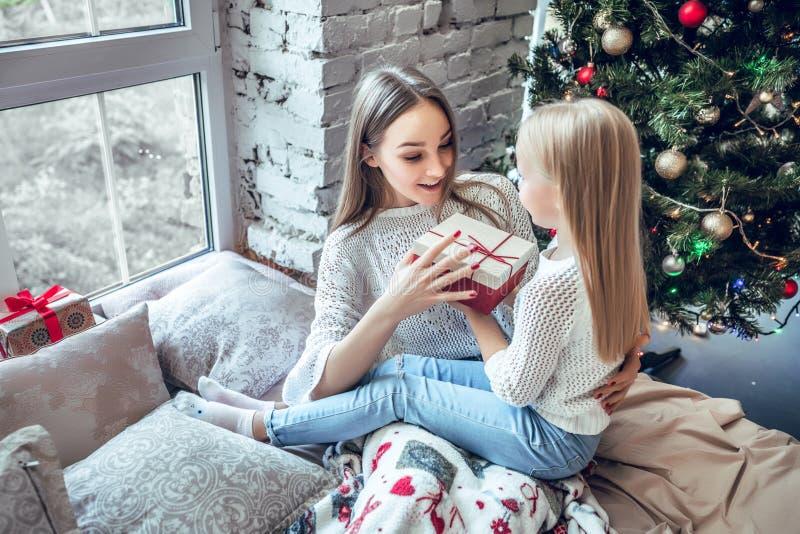 Glückliche Mutter und Tochter mit Geschenkbox über Raum mit Weihnachtsbaumhintergrund stockfoto