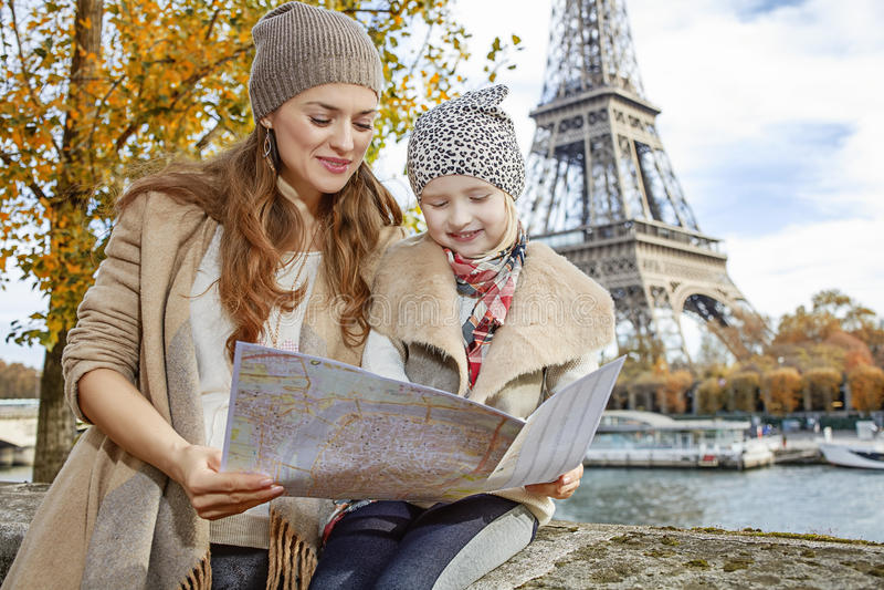 Glückliche Mutter- und Tochtertouristen, welche die Karte in Paris betrachten lizenzfreie stockbilder