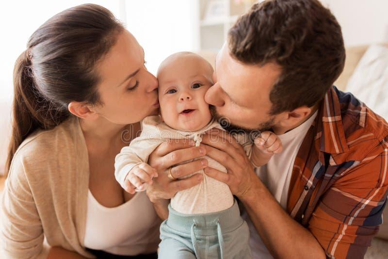 Glückliche Mutter und Vater, die zu Hause Baby küsst stockfotografie