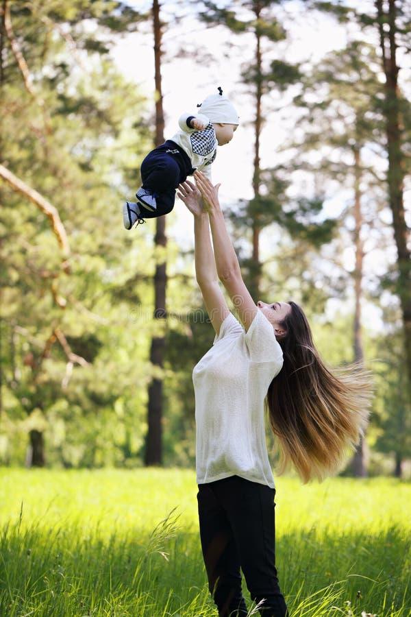 Glückliche Mutter wirft oben ihren Sohn stockbild
