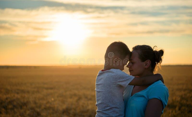 Glückliche Mutterküsse auf dem Stirnbaby, das an im Sonnenlicht ein Weizenfeld, Familie auf einem Weizengebiet auf dem Sonnenunte lizenzfreie stockbilder