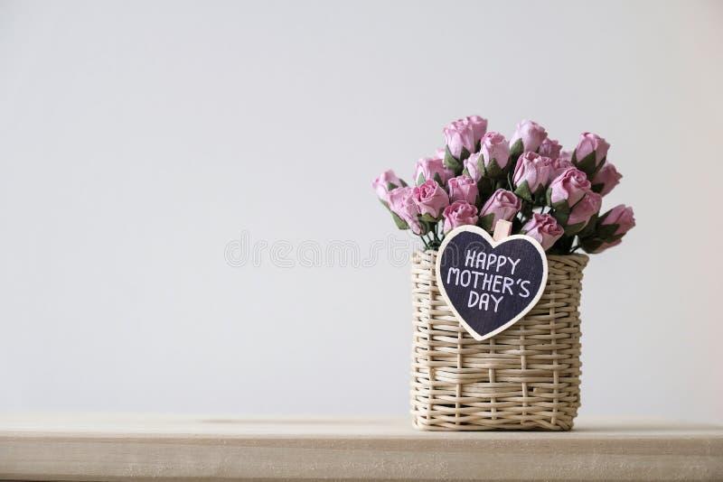 Glückliche Muttertagesmitteilung auf hölzernem Herzen und rosa Papierrosen stockfoto