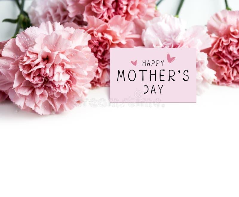 Glückliche Muttertagesmitteilung auf Papier- und rosa Gartennelkenblume stockbild