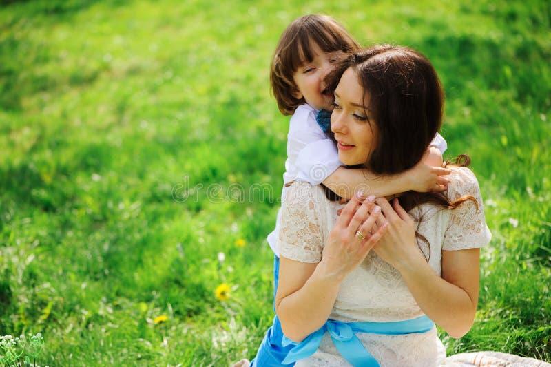 glückliche Mutterumarmungen und Kusskleinkind scherzen den Sohn, der im Frühjahr im Freien sind oder Sommer lizenzfreie stockbilder