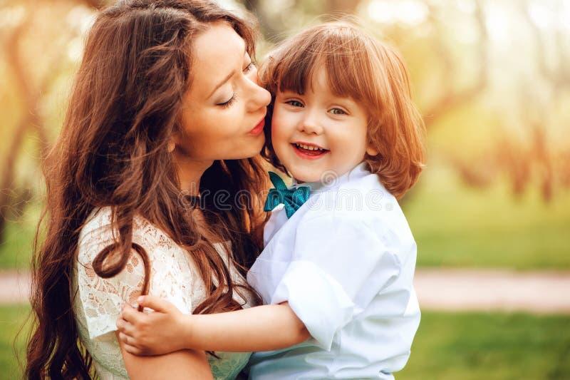 glückliche Mutterumarmungen und Kusskleinkind scherzen den Sohn, der im Frühjahr im Freien sind oder Sommer stockbild