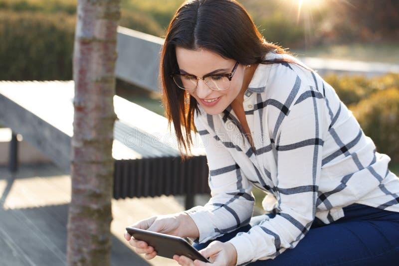 Glückliche Nachrichten der jungen Frau Leseauf Tablette lizenzfreies stockbild