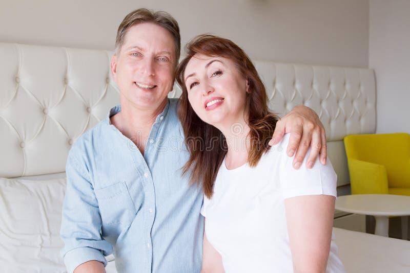 Glückliche Nahaufnahmeleutegesichter Lächelnde Mittelalterpaare zu Hause Familienspaß-Zeitwochenende und starke Liebesbeziehung G lizenzfreies stockbild