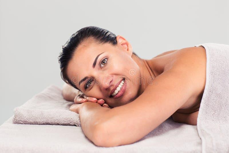 Glückliche nette Frau, die auf Massageruhesessel liegt lizenzfreie stockbilder