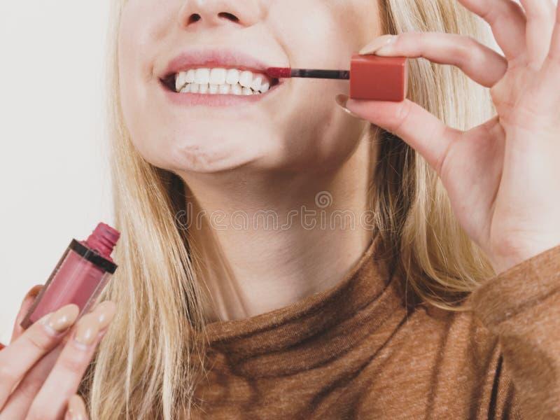Glückliche nette Frau, die Lippenglanz verwendet lizenzfreie stockfotografie