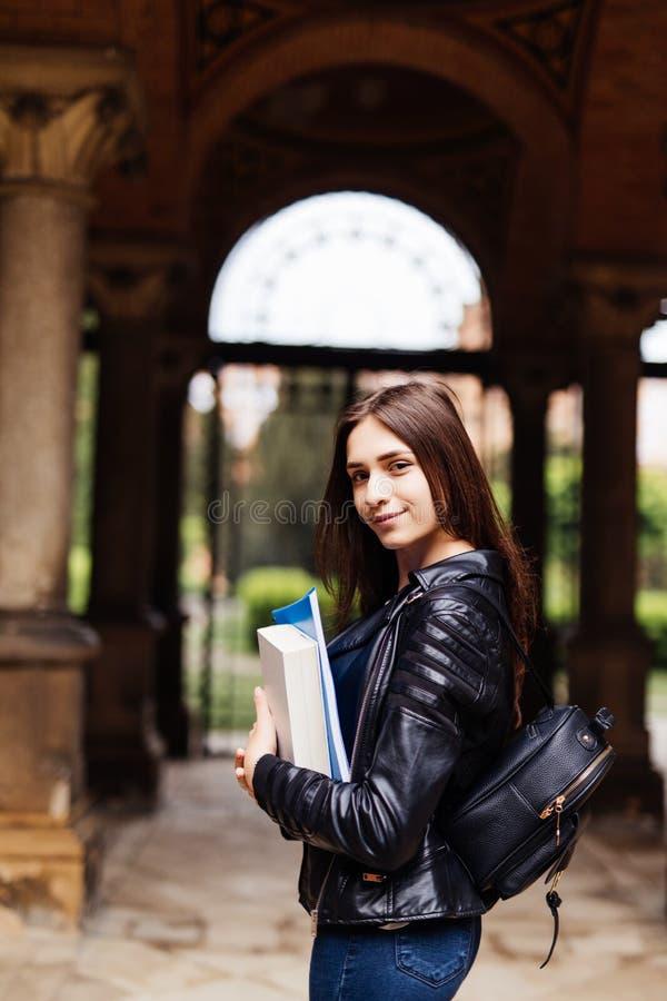 Glückliche nette junge Studentin mit dem Rucksack, der Bücher hält und draußen geht lizenzfreies stockbild