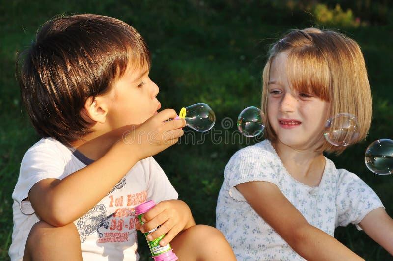 Glückliche nette Kinder, die mit Luftblasen spielen lizenzfreie stockbilder