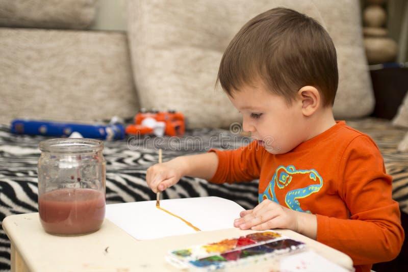 Glückliche nette Kinderzeichnung mit Bürste unter Verwendung der Werkzeuge einer Malerei Hand, die lego Wand aufbaut Kinder, Kind lizenzfreies stockbild