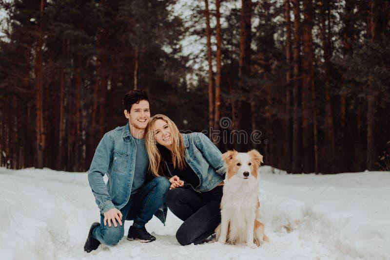 Glückliche nette lächelnde Paare von jungen Leuten in den Denimklagen im schneebedeckten Wald im Winter mit rotem Hund border col lizenzfreie stockbilder