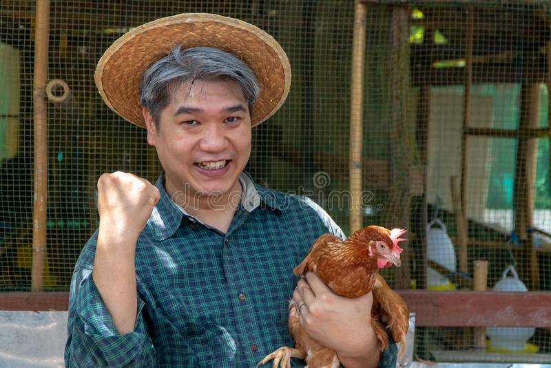 Glückliche organische Mitte alterte Landwirtgriffhuhn in seinen Armen vor Hühnerstall in der Landschaft Landwirt ist für Erfolg f stockbild