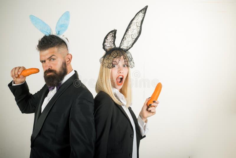 Glückliche Ostereipaare Lächeln Ostern Nettes Häschen essen Karotten Osterhasenkleid lizenzfreie stockbilder