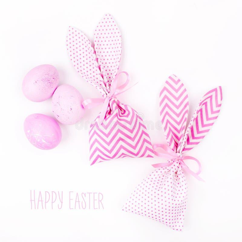 Glückliche Ostern-Grußkarte Häschenfestlichkeit bauscht sich mit den rosa Eiern, die auf weißem Hintergrund lokalisiert werden lizenzfreies stockbild