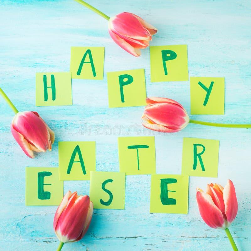 Glückliche Ostern-Hintergrundtulpen blüht Hand geschriebene Briefe lizenzfreies stockfoto