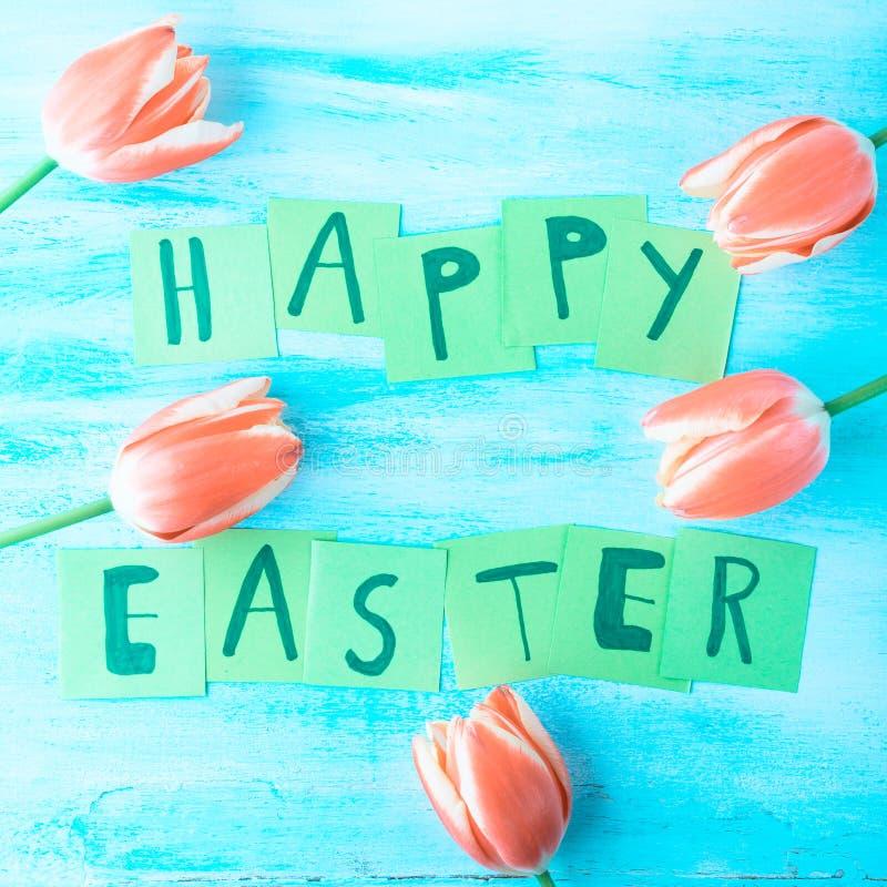 Glückliche Ostern-Hintergrundtulpen blüht Hand geschriebene Briefe lizenzfreie stockfotos