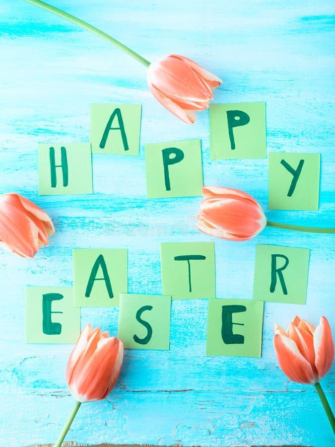 Glückliche Ostern-Hintergrundtulpen blüht Hand geschriebene Briefe lizenzfreie stockbilder