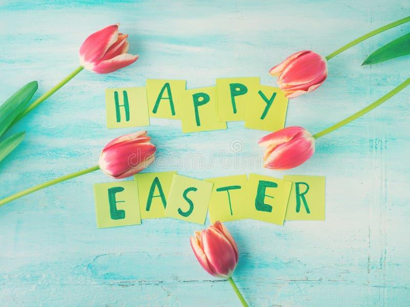 Glückliche Ostern-Hintergrundtulpen blüht Hand geschriebene Briefe stockbilder