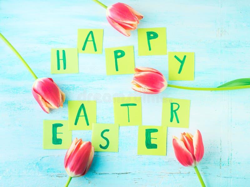 Glückliche Ostern-Hintergrundtulpen blüht Hand geschriebene Briefe lizenzfreie stockfotografie