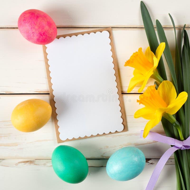 Glückliche Ostern-Karte mit Eiern in Folge auf Unterseite mit Narzissen-Blumen auf der Seite des weißen Shiplap-Brett-Hintergrund stockfotografie