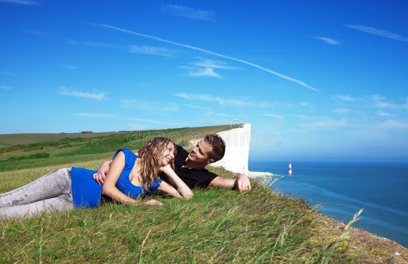 Glückliche Paare auf dem Rand einer Klippe stockfotografie