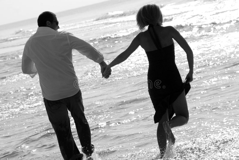 Glückliche Paare in der Brandung stockbild