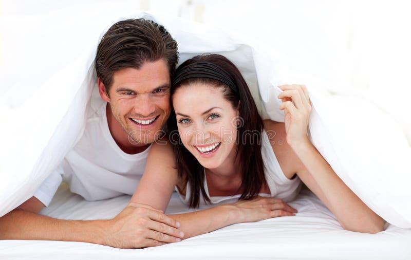 Glückliche Paare, die auf Bett liegen lizenzfreies stockbild