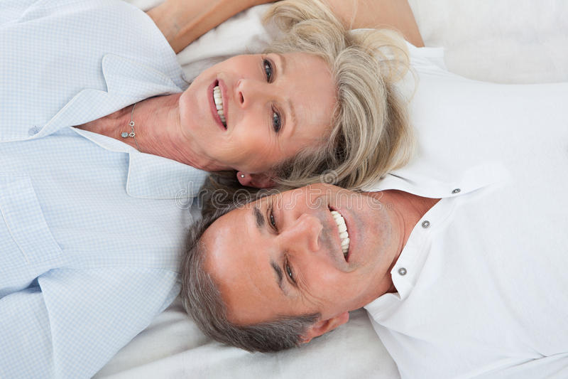 Glückliche Paare, die auf Bett liegen lizenzfreies stockfoto