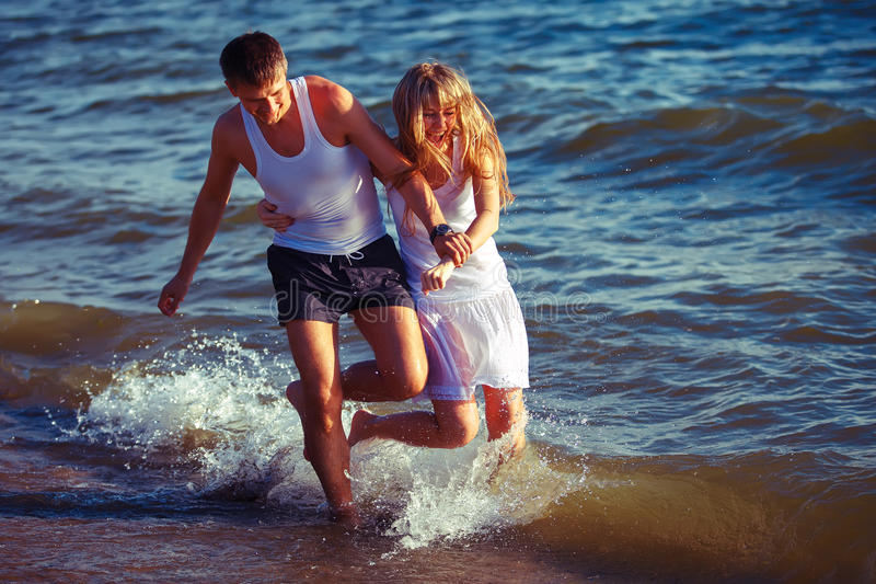 Glückliche Paare, die auf den Strand laufen lizenzfreie stockfotos