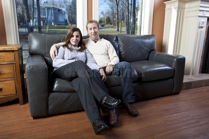 Glückliche Paare, die auf einer Couch sitzen stockfotografie