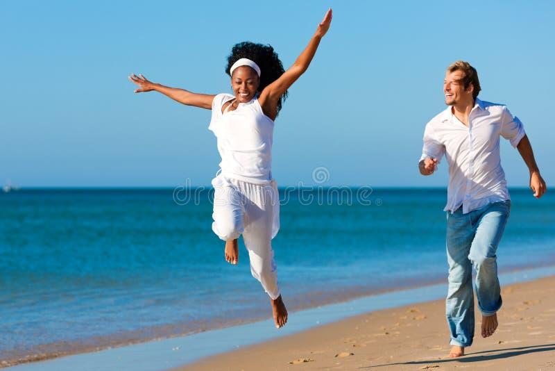 Glückliche Paare, die auf Strand gehen und laufen lizenzfreies stockfoto