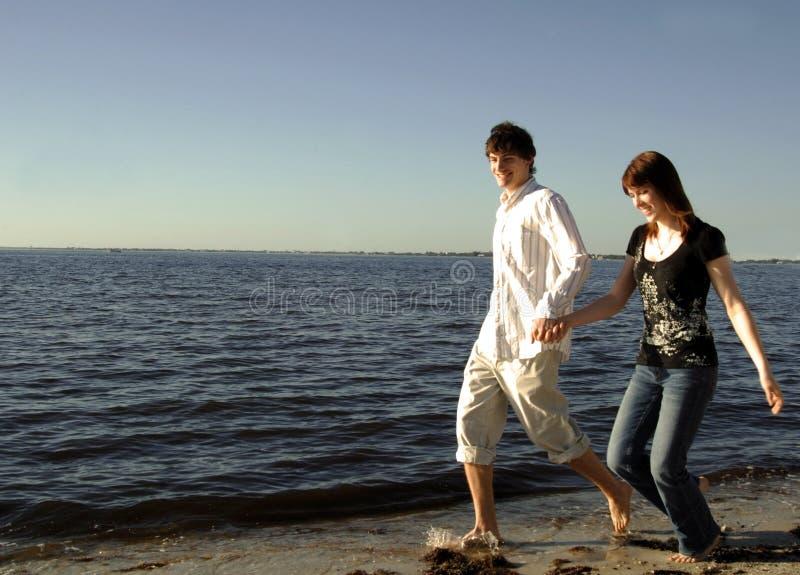Glückliche Paare, die auf Strand laufen stockfotografie