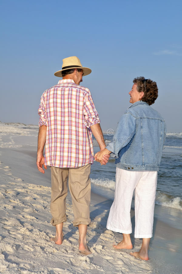Glückliche Paare, die auf Strand am Sonnenuntergang schlendern lizenzfreie stockfotografie