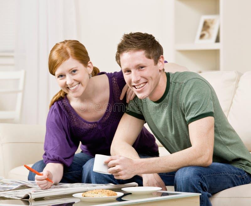 Glückliche Paare, die durch eingestufte Anzeigen suchen stockbild
