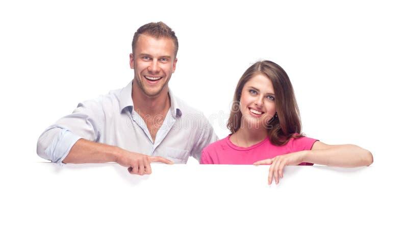 Glückliche Paare, die eine unbelegte Anschlagtafel anhalten lizenzfreie stockfotos
