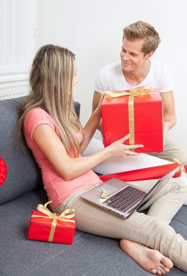 Glückliche Paare, die Geschenke austauschen stockfoto