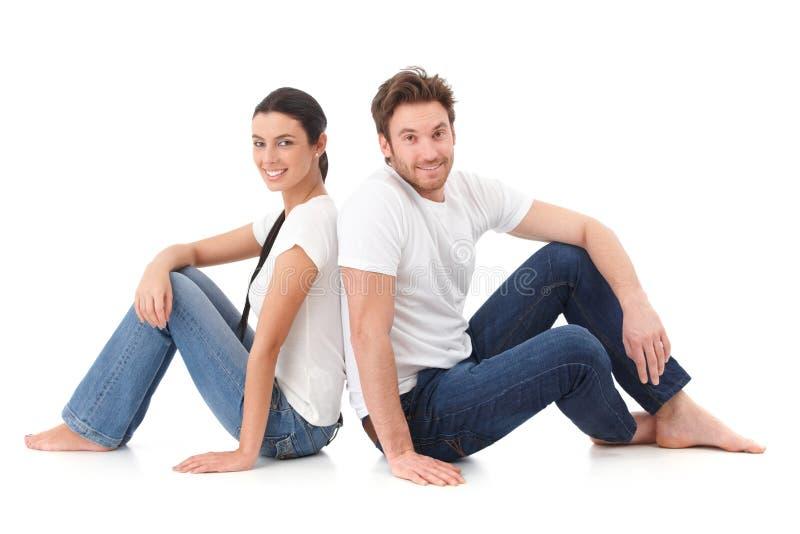Glückliche Paare, die mit zurück zu einander sitzen lizenzfreie stockbilder