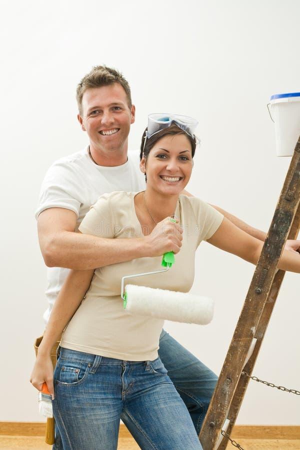 Glückliche Paare, die nach Hause verbessern lizenzfreies stockfoto