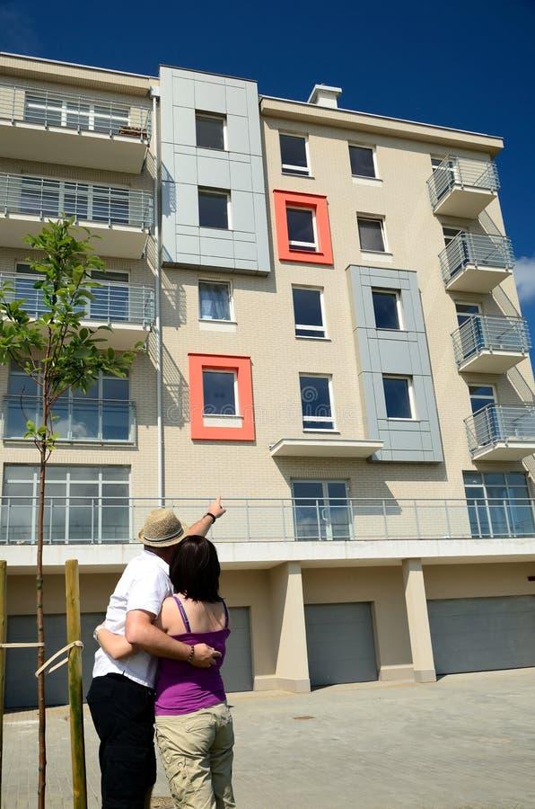 Glückliche Paare, die nach neuen Wohnungen suchen lizenzfreies stockbild